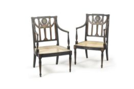 A pair of George III ebonised and painted open armchairs