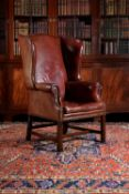 A mahogany and red leather upholstered wing armchair
