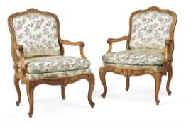 A pair of Louis XV carved beech and upholstered fauteuil