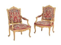 A pair of carved giltwood open armchairs