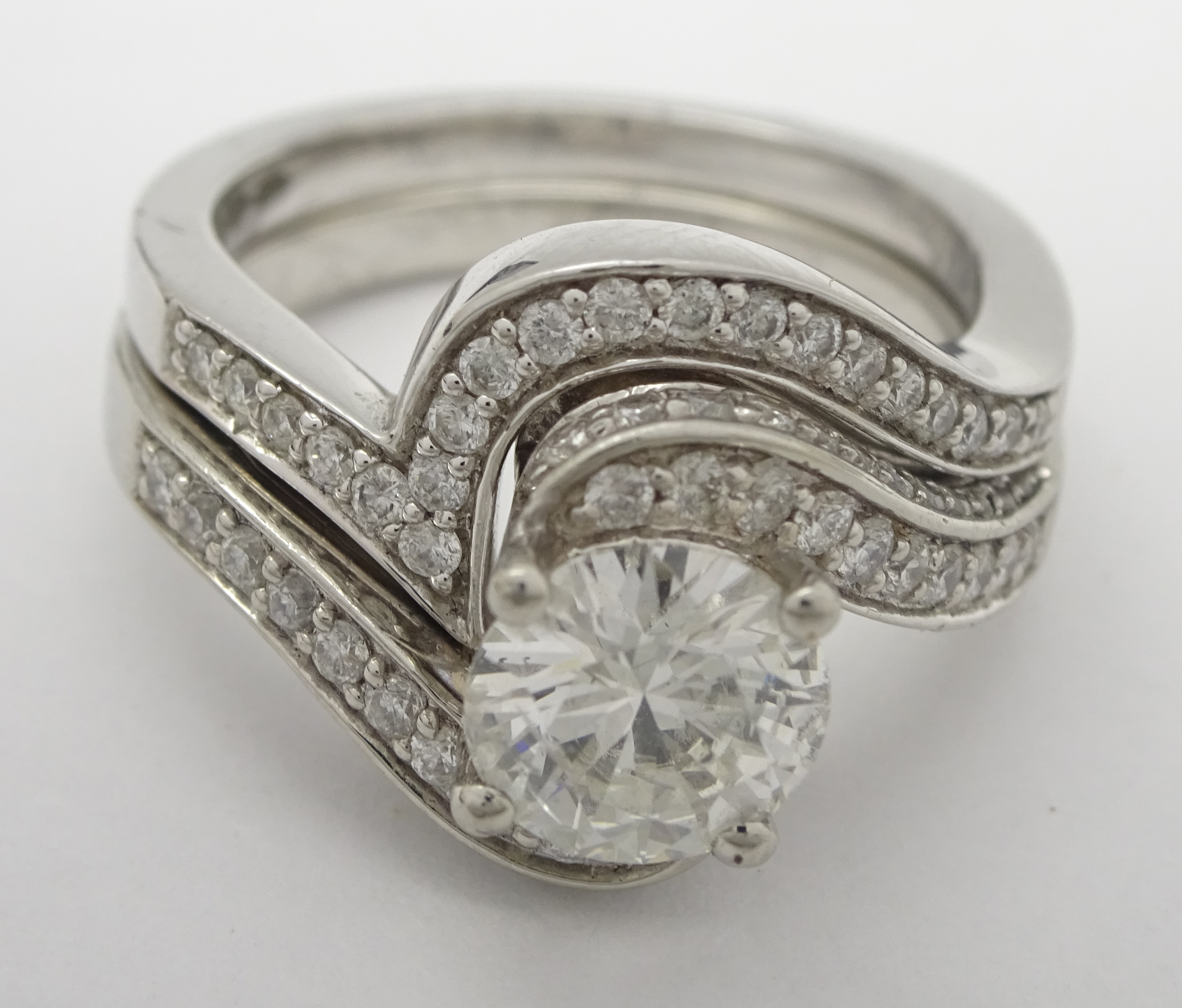 Lot 1035 - Two platinum rings, one set with a round brilliant cut diamond and diamond shoulders,