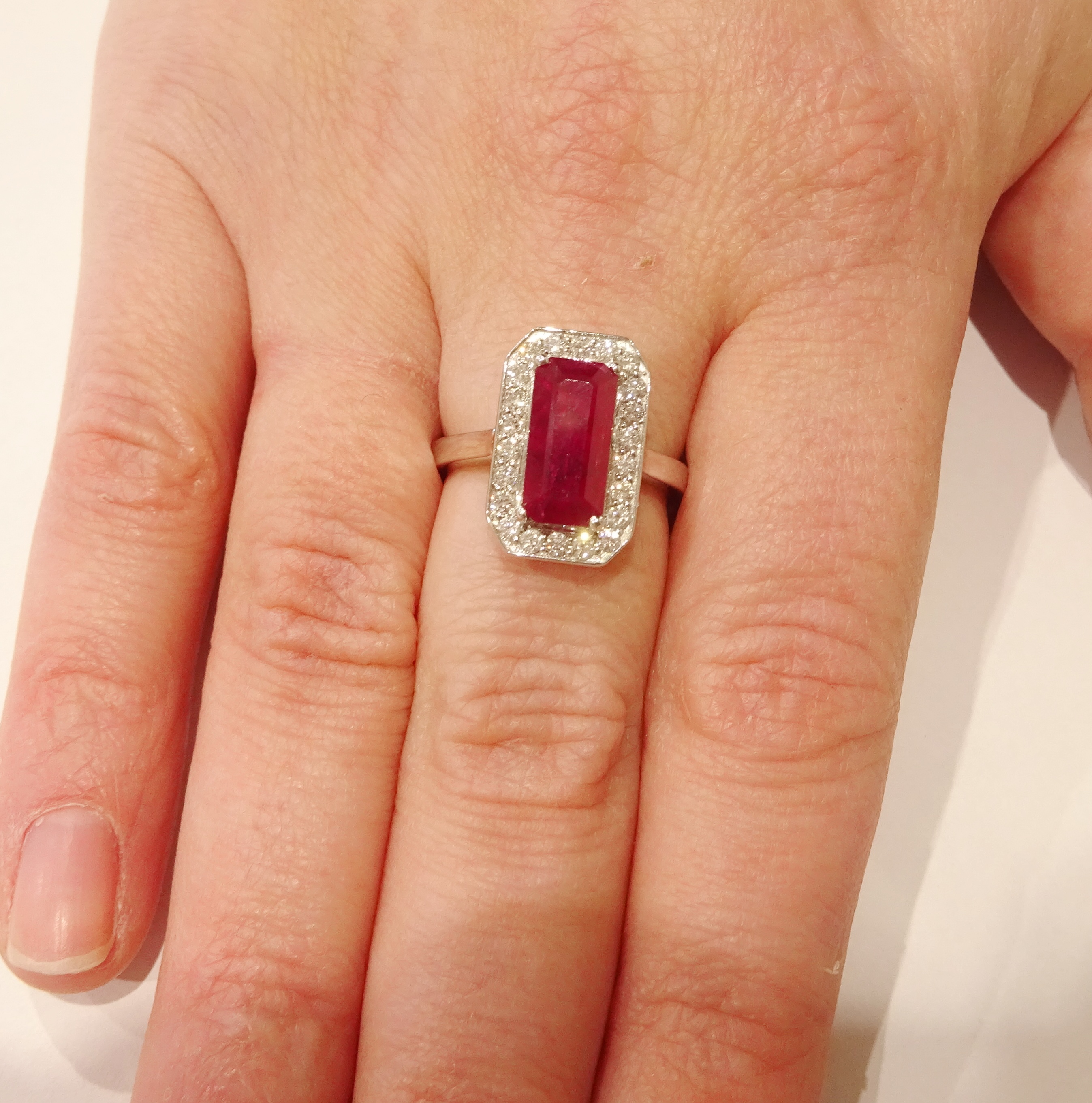 Lot 1027 - 18ct white gold emerald cut ruby and round brilliant cut diamond cluster ring, hallmarked,