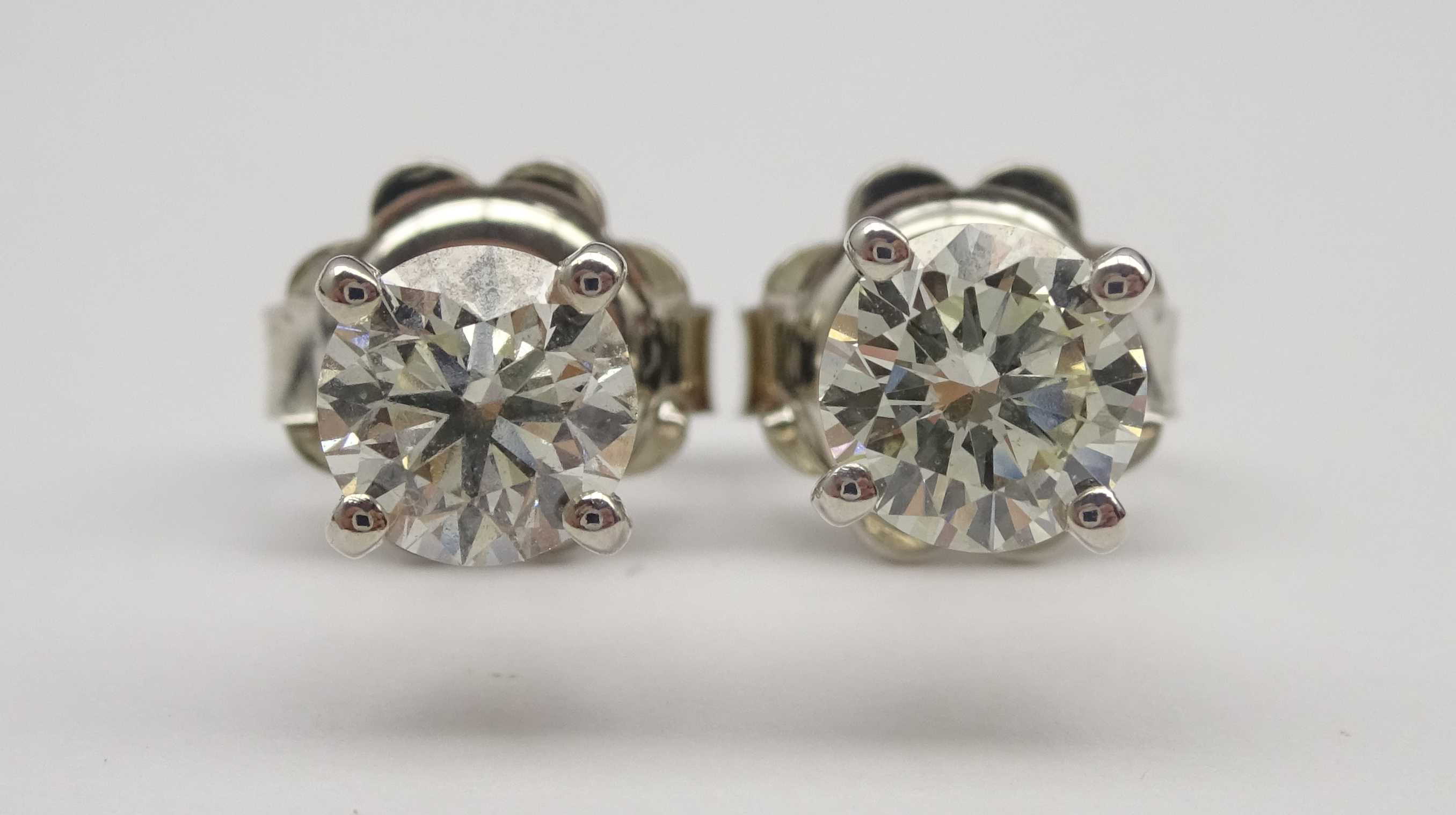 Lot 1022 - Pair of 18ct white gold, round brilliant cut diamond stud earrings, stamped 750,