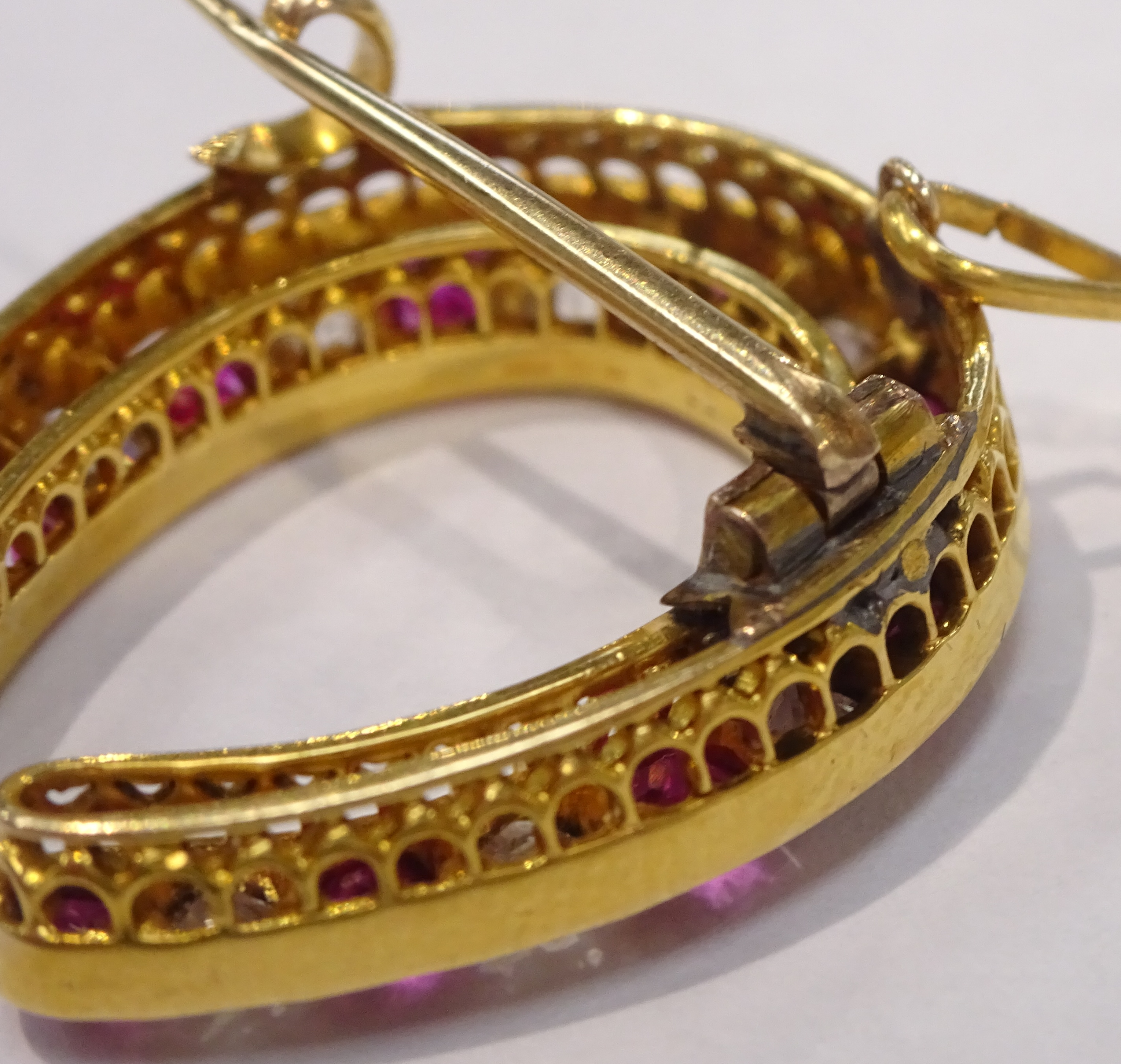 Lot 1003 - Early 20th century gold ruby and old cut diamond horseshoe brooch Condition Report &