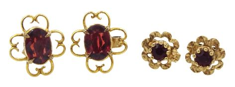 Pair of gold oval garnet stud earrings, open work design and one other similar pair, both 9ct stampe