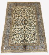 Persian fine Kashan ivory ground carpet, with repeating floral motif enclosed by multi line border,
