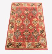 Persian design Heriz red ground rug, with repeating medallion on red field, enclosed by guarded bord