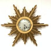 Elliot Giltwood starburst wall clock with silvered dial and Roman numeral chapter ring, retailed by