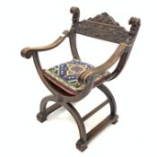 Early 20th century walnut 'X' framed chair, with floral and mask carved cresting rail and scrolled o