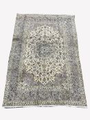 Persian ivory ground rug, central star motif enclosed by interlaced foliate, with multi line border,