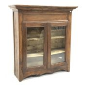 19th century French oak and walnut armoire, projecting cornice over to glazed doors enclosing two sh