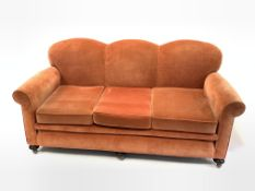 Early to mid 20th century three seat sofa, with serpentine back over loose cushions, raised on turne