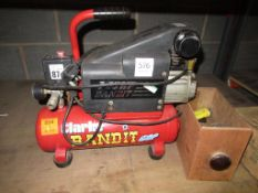 A Clarke Bandit Air Compressor with a box of assorted gauges and connectors