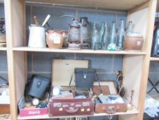 Two shelves of bottles/lamps, binoculars etc