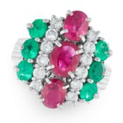 A RUBY, EMERALD AND DIAMOND DRESS RING in platinum, set with a trio of graduated oval cut rubies