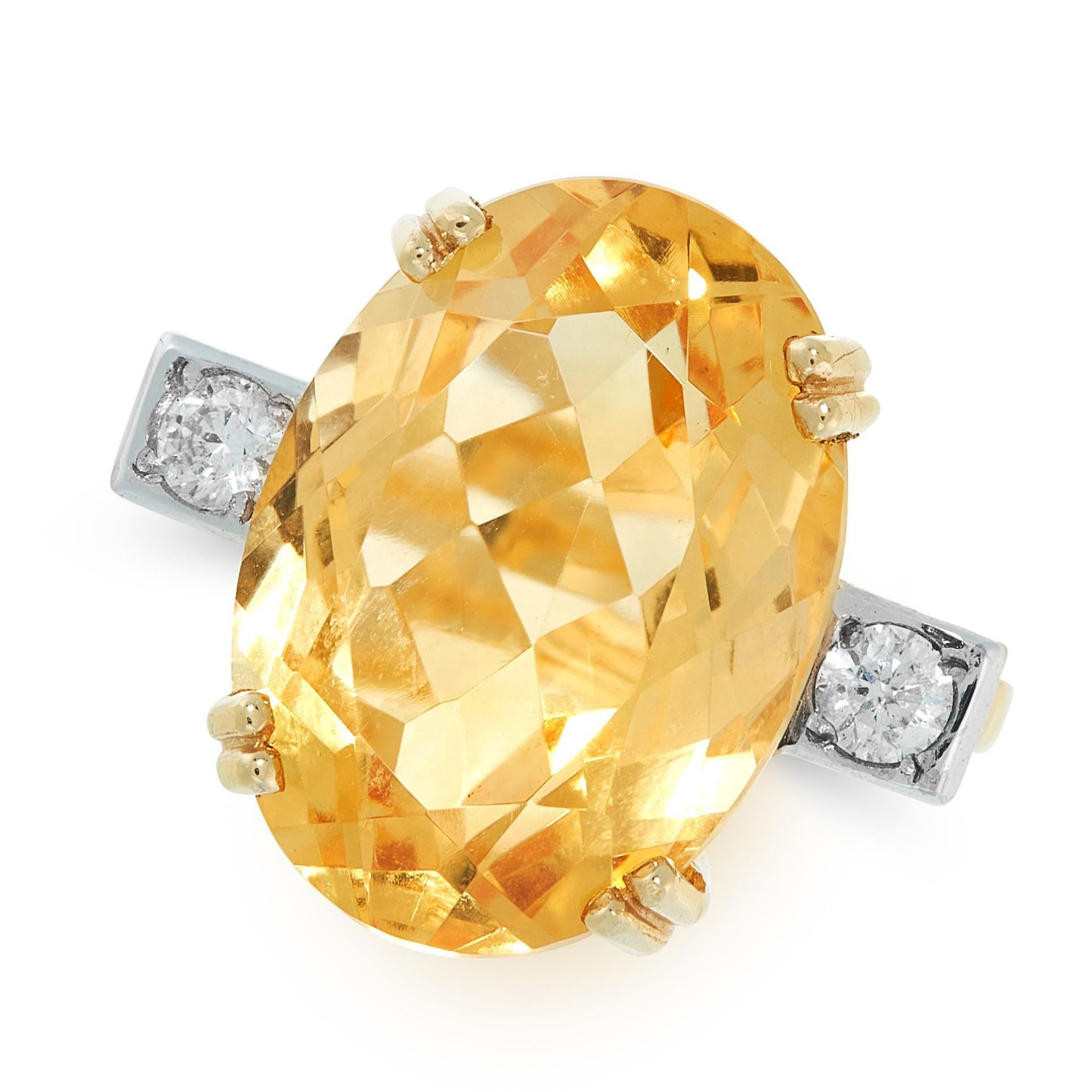 A CITRINE AND DIAMOND DRESS RING in 18ct yellow gold, set with an oval cut citrine between two round