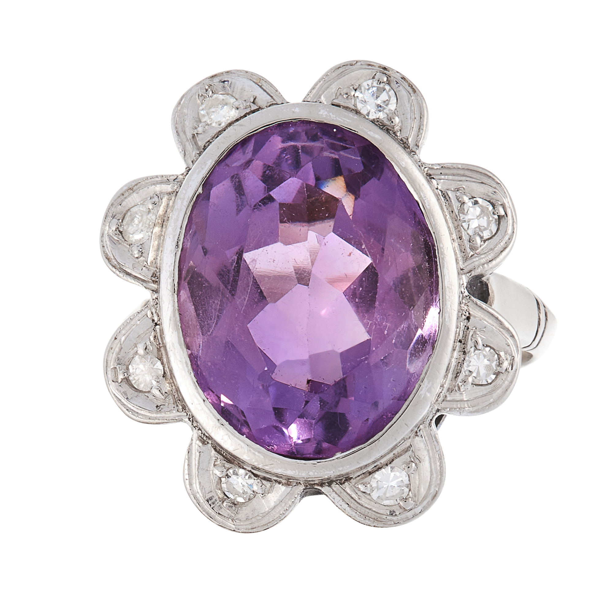 AN AMETHYST AND DIAMOND DRESS RING in white gold, set with an oval cut amethyst within a scalloped