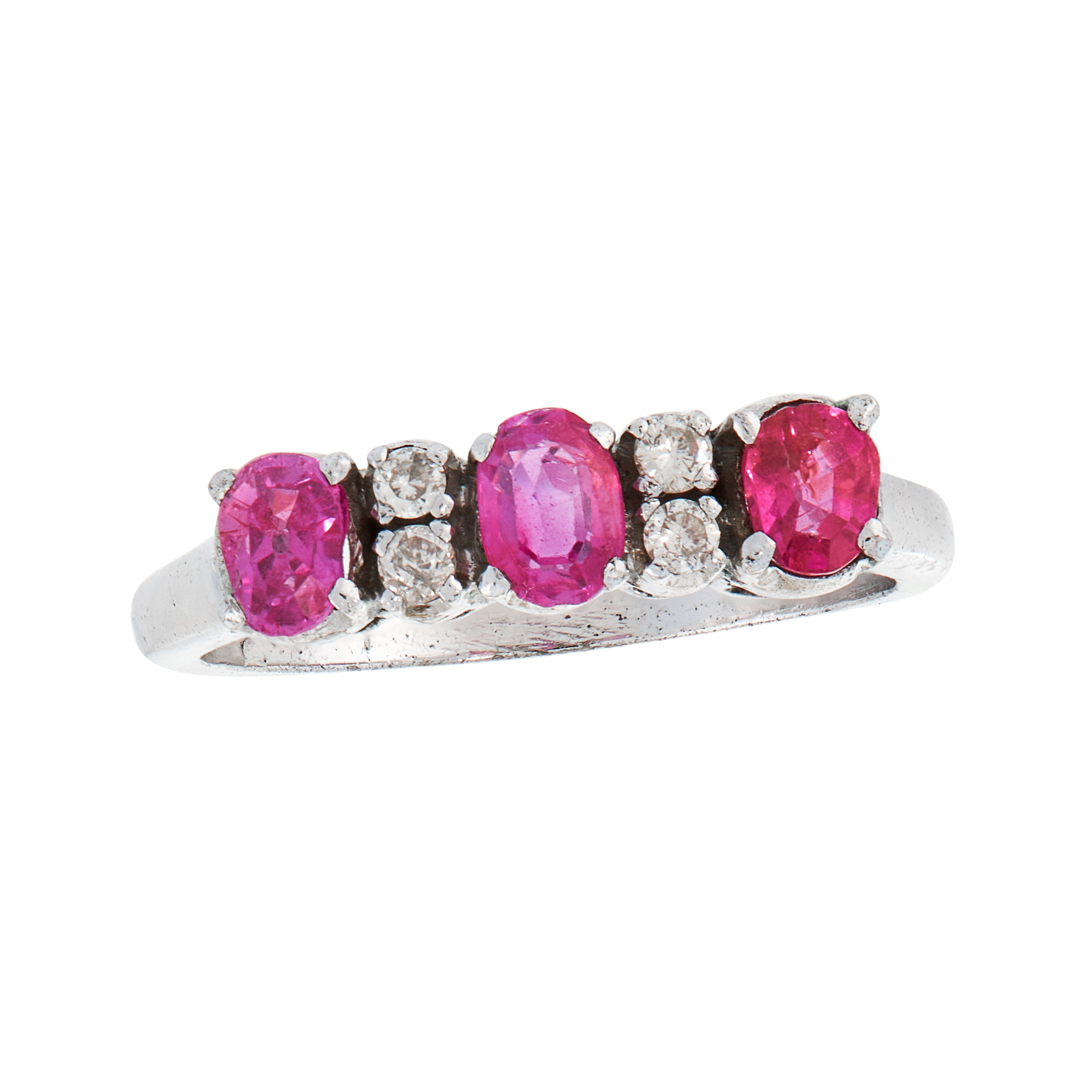 A RUBY AND DIAMOND DRESS RING set with a trio of graduated oval cut rubies punctuated by pairs of