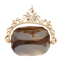 AN ANTIQUE CITRINE / QUARTZ FOB SEAL PENDANT in yellow gold, of scrolling design, set with a