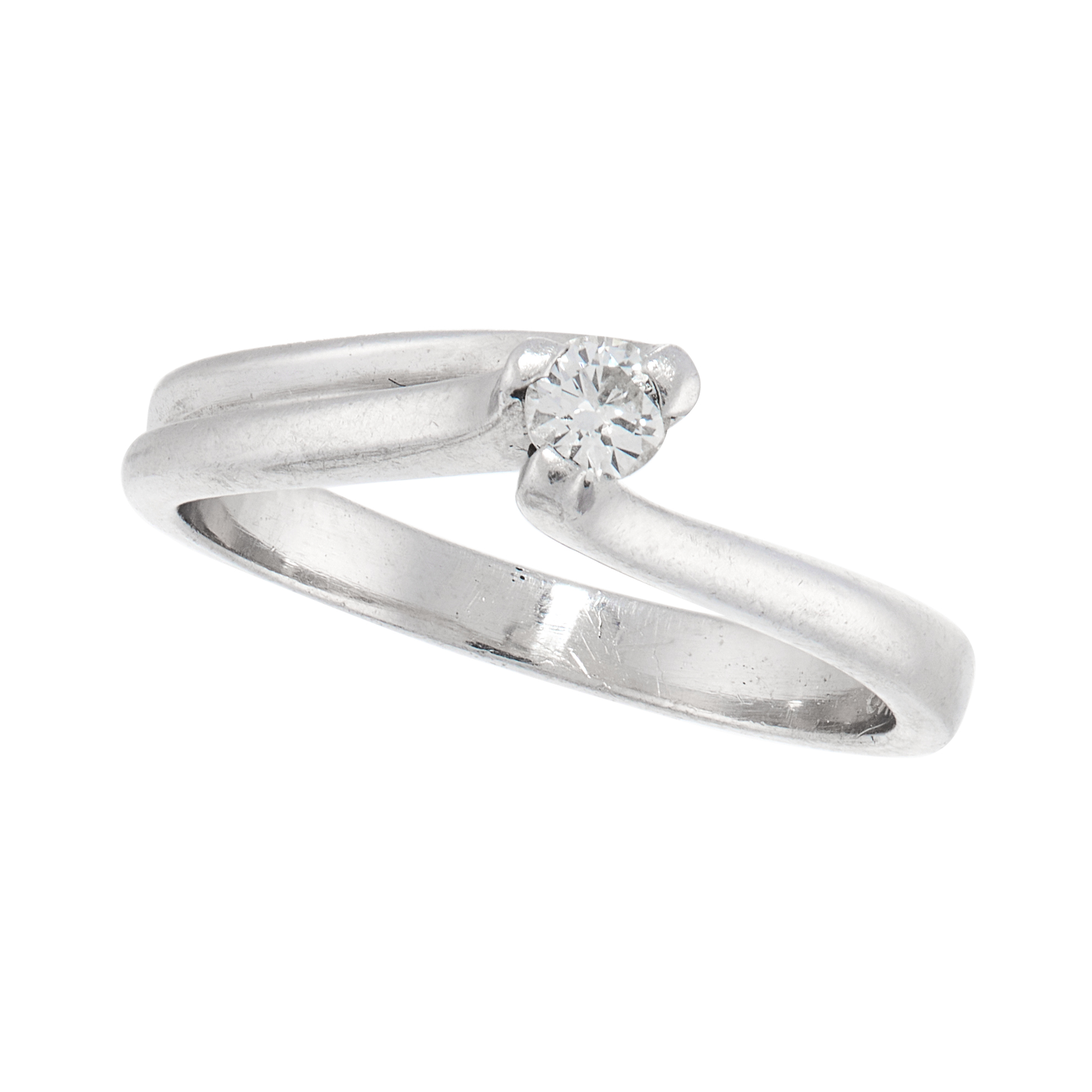 A SOLITAIRE DIAMOND DRESS RING in platinum, set with a round cut diamond within a stylised twisted