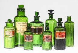 A GROUP OF EIGHT LATE VICTORIAN GREEN GLASS APOTHECARY BOTTLES