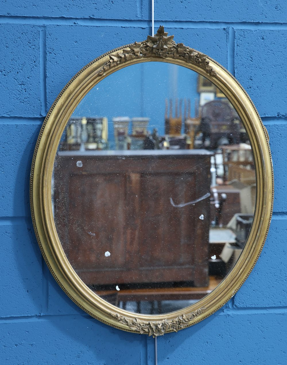 Lot 1419 - A VICTORIAN GILT-COMPOSITION OVAL MIRROR