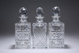 THREE LARGE SQUARE-SECTION GLASS DECANTERS.