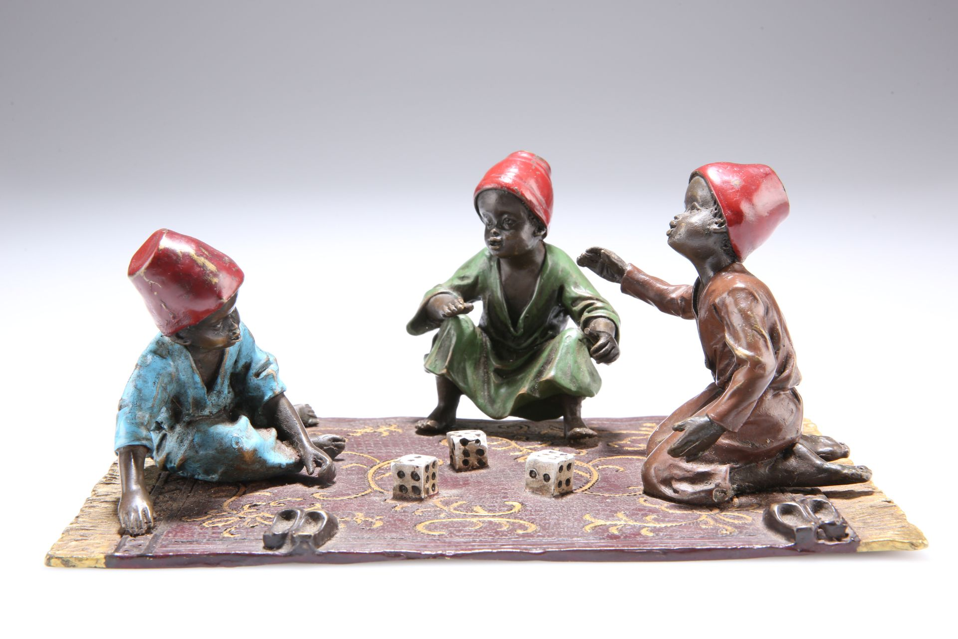 AFTER FRANZ BERGMAN, A COLD-PAINTED BRONZE GROUP, depicting three Arab boys playing dice on a