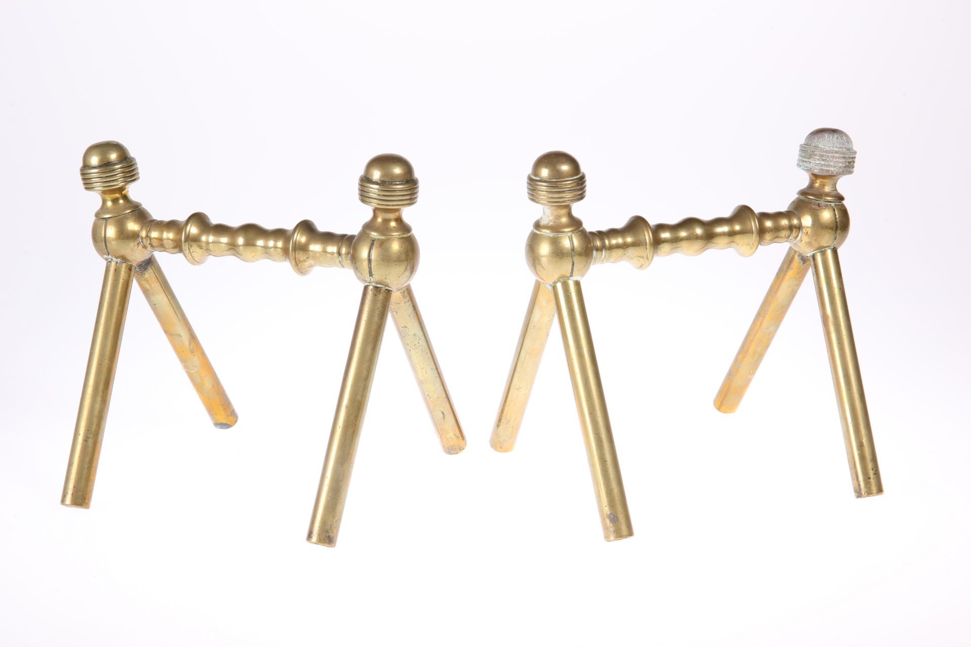 A PAIR OF AESTHETIC MOVEMENT BRASS FIREDOGS IN THE MANNER OF CHRISTOPER DRESSER, CIRCA 1880,