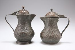 TWO 18TH CENTURY COPPER JUGS AND COVERS, each with hinged domed cover, repousse with scrolling