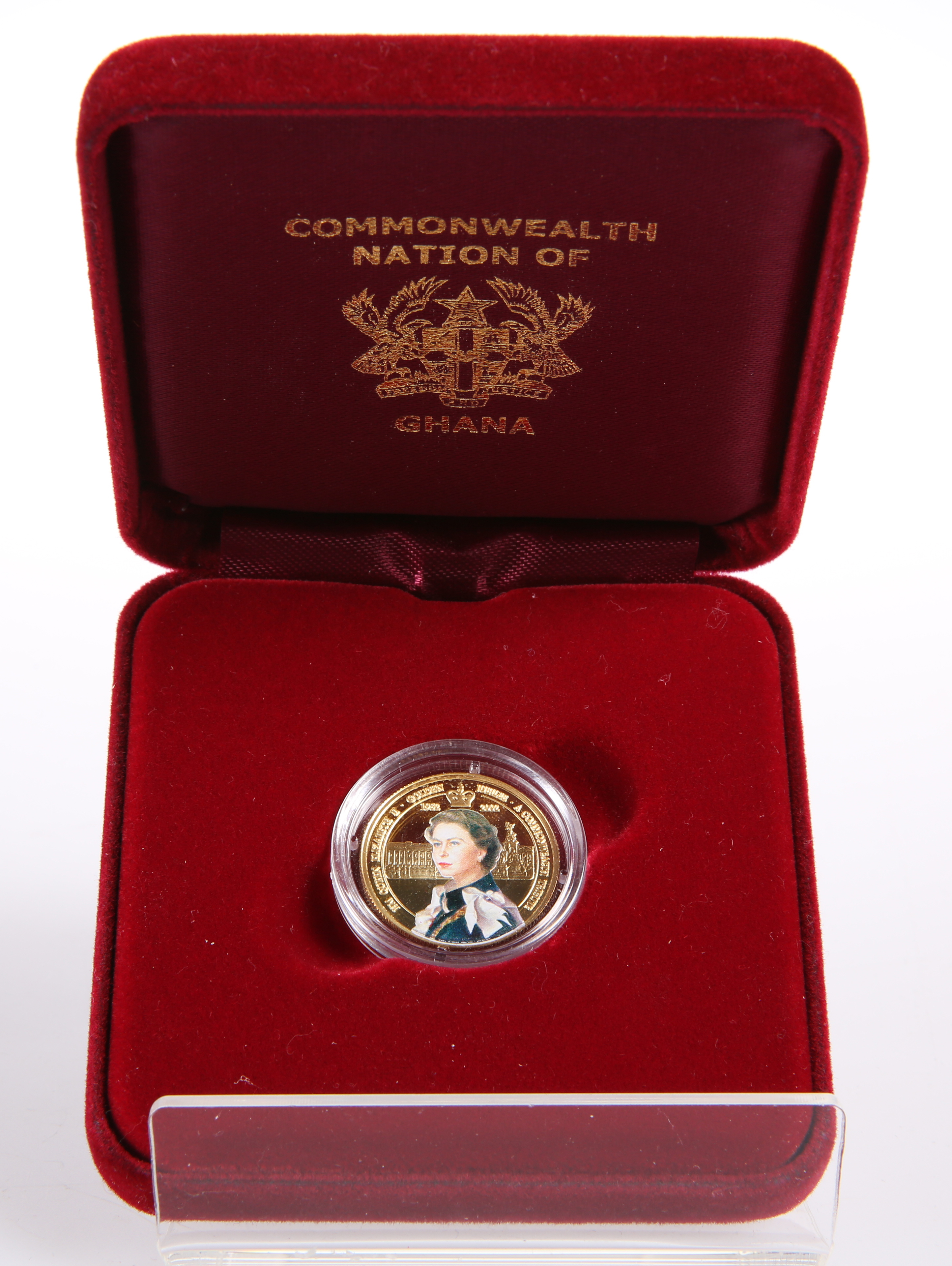 A GHANIAN 500 SIKA 9 CARAT GOLD AND ENAMELLED COMMONWEALTH TRIBUTE COIN, boxed