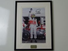 AUTOGRAPH: LEWIS HAMILTON - A framed and glazed signed colour 10 x 8 photograph - this item has been