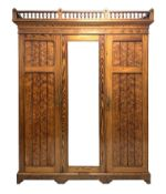 Late Victorian pitch pine triple wardrobe, turned gallery pediment over projecting cornice,
