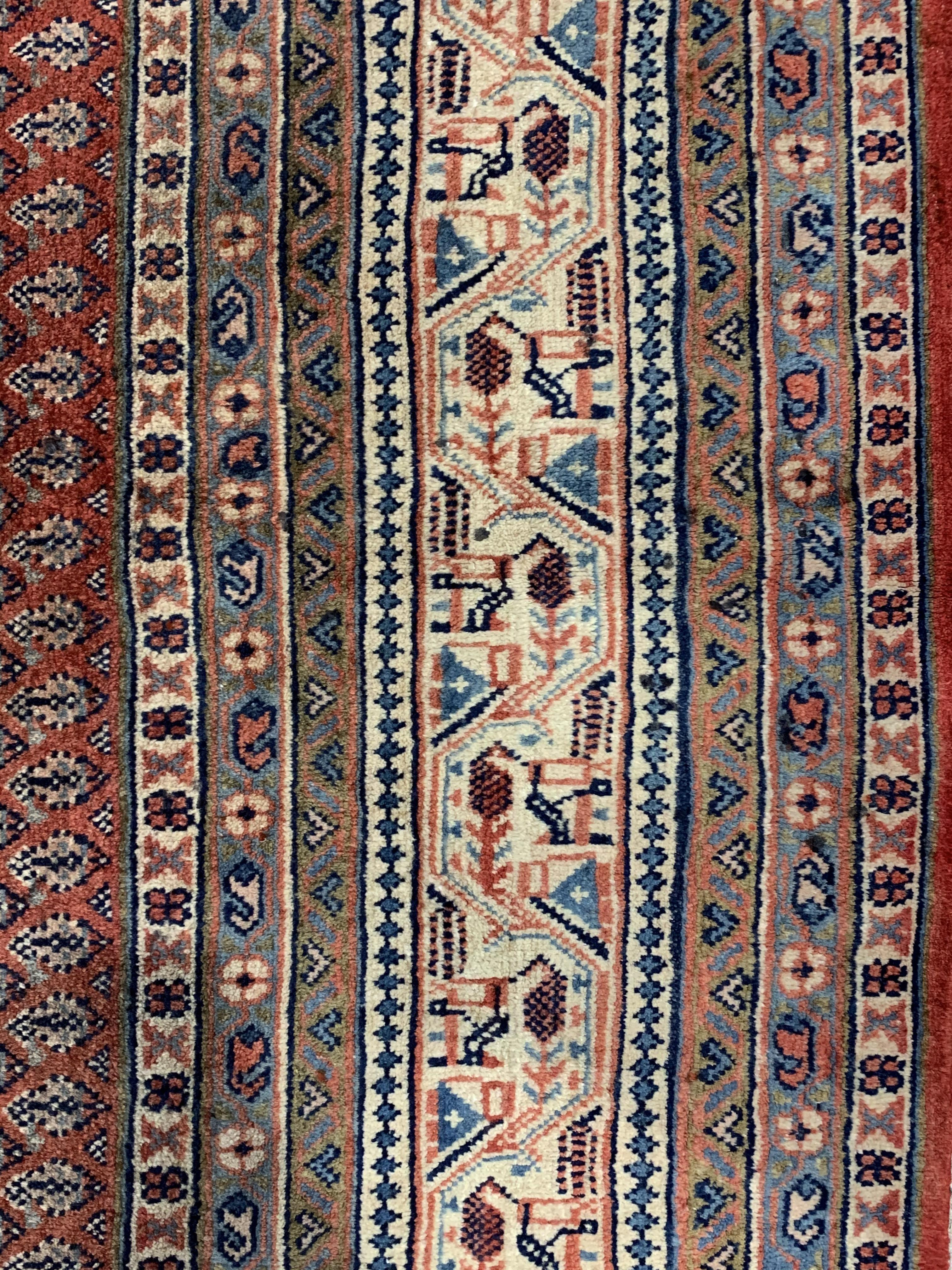 Large Persian Araak carpet, red ground field decorated all over with Boteh motifs, multiple band - Image 3 of 4