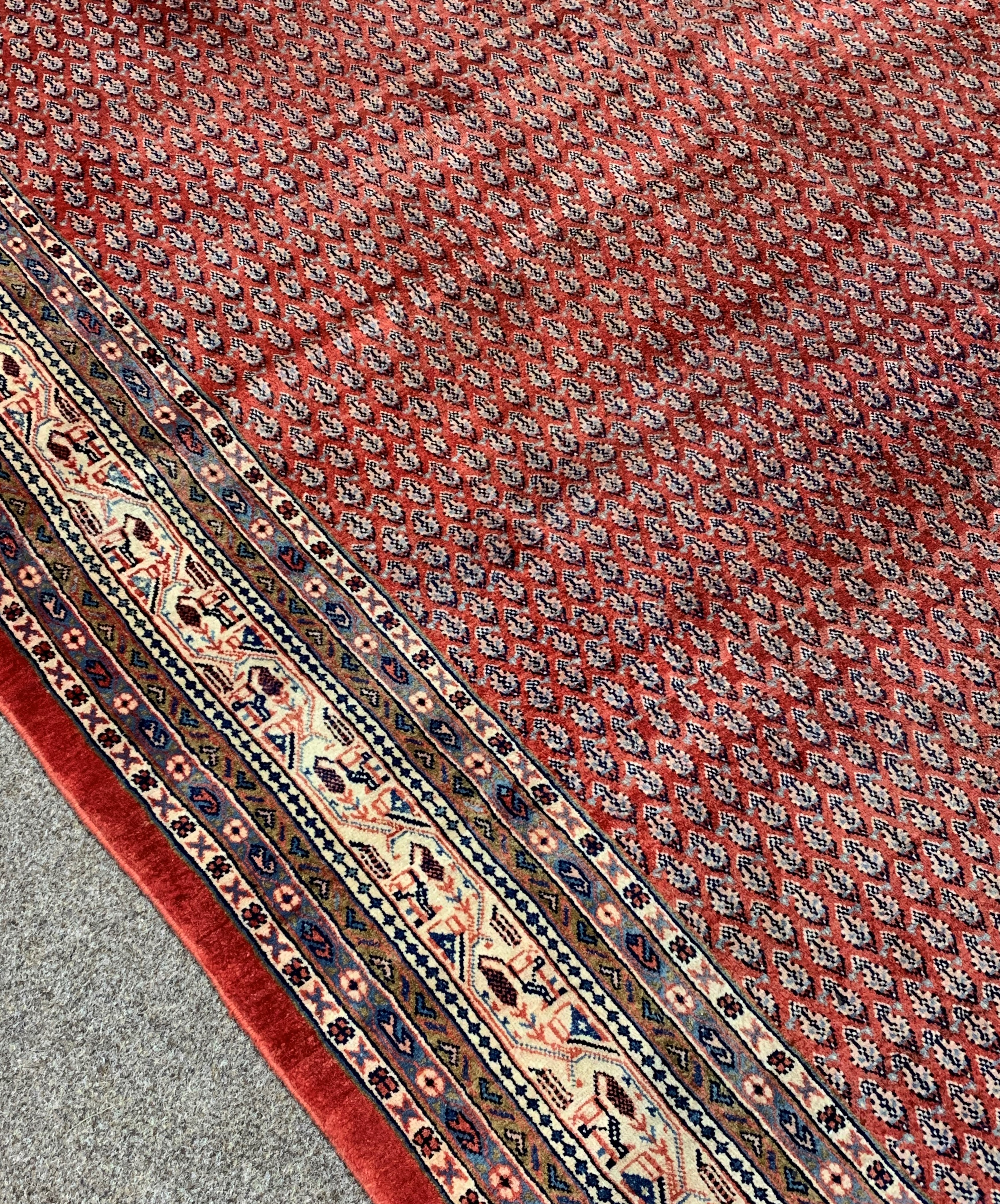 Large Persian Araak carpet, red ground field decorated all over with Boteh motifs, multiple band - Image 2 of 4