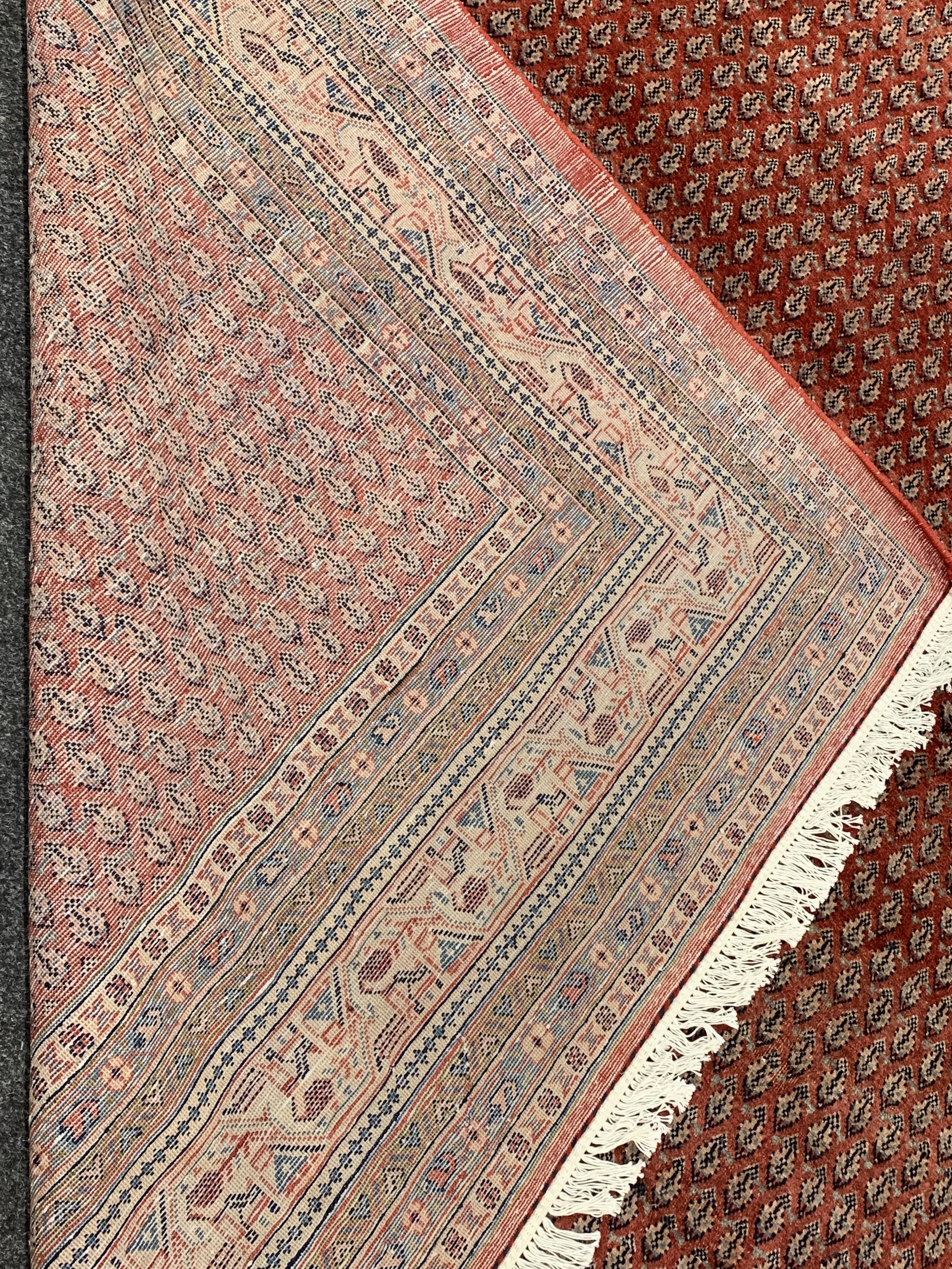 Large Persian Araak carpet, red ground field decorated all over with Boteh motifs, multiple band - Image 4 of 4