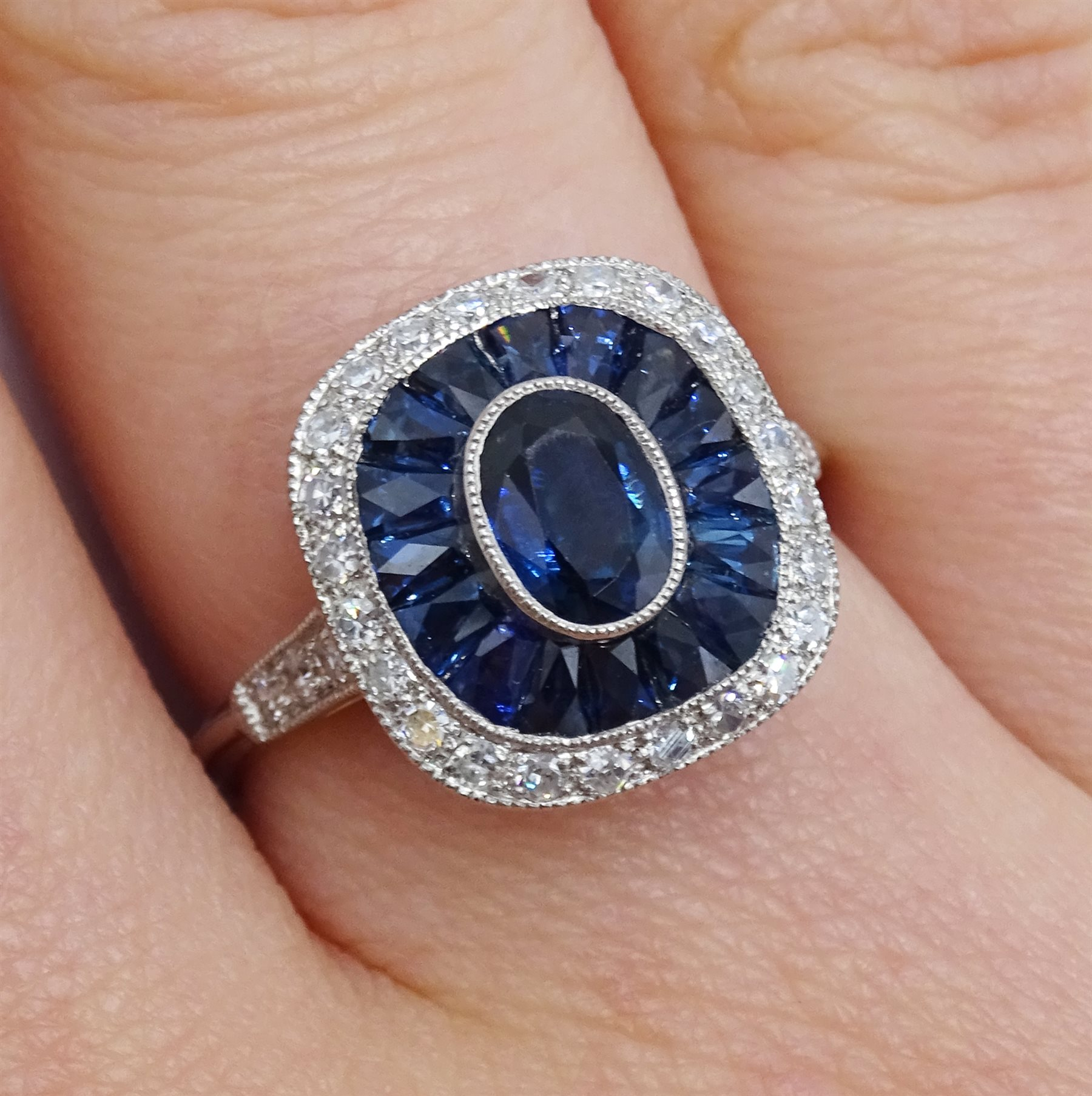 Platinum sapphire and diamond ring, the central oval sapphire surrounded by halo of calibre cut - Image 2 of 5