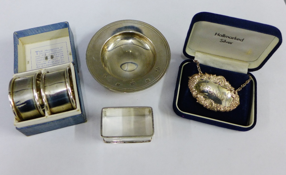 Lot 31 - Three Birmingham silver napkin rings, a silver Brandy decanter label and a QEII silver armada