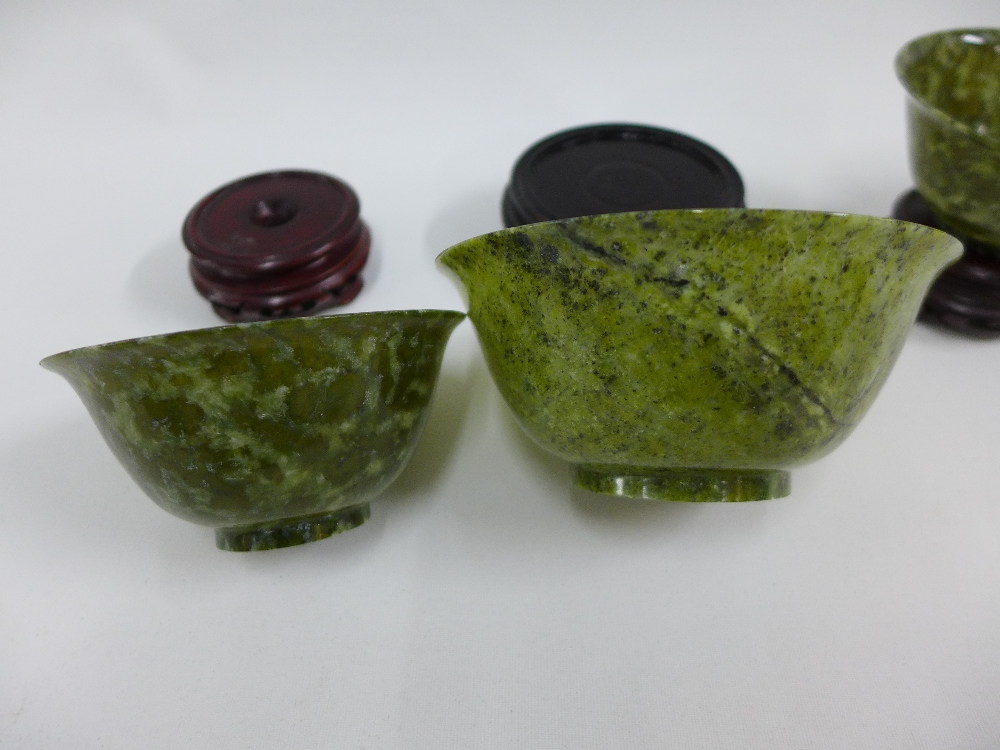 Lot 200 - Three green jadeite bowls, largest 13 x 6cm (3)