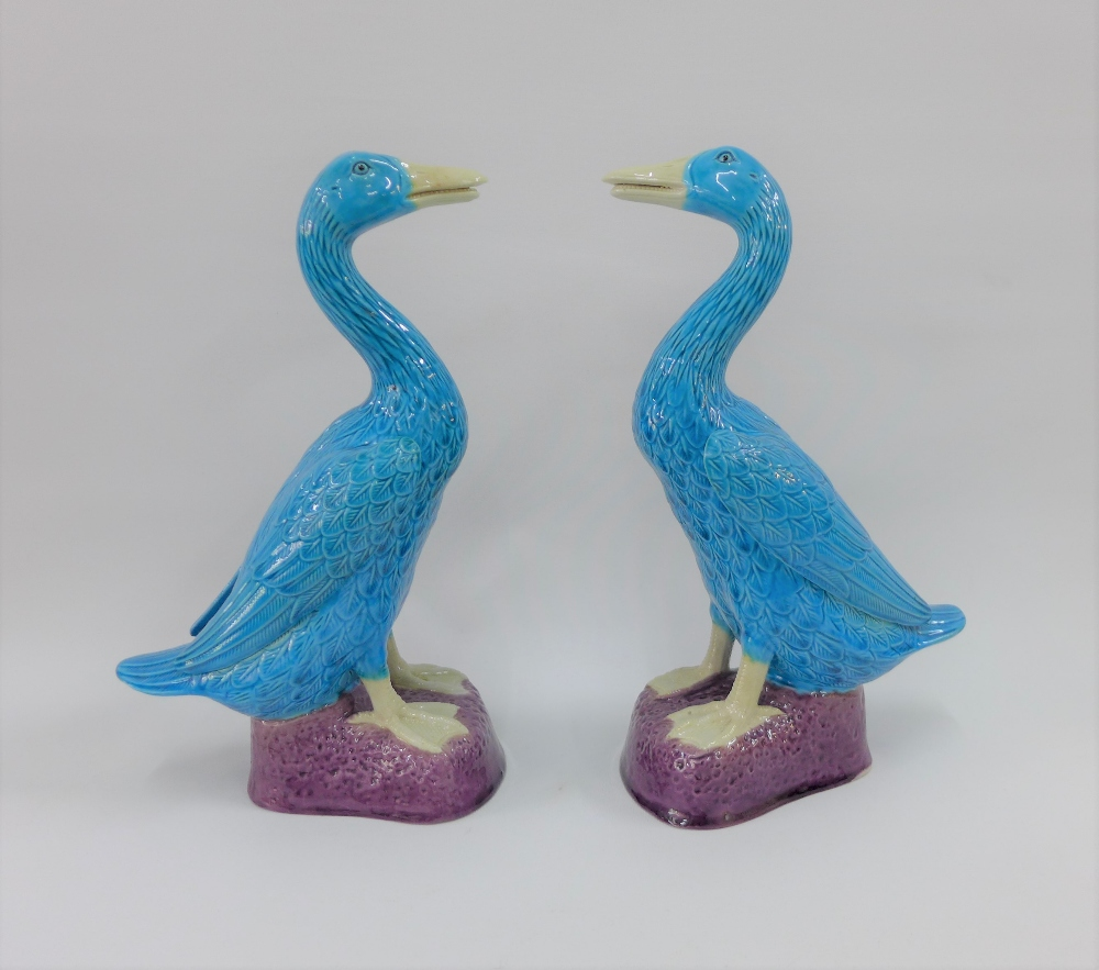 Lot 125 - A pair of Chinese turquoise blue glazed duck figures on purple bases, 30cm high