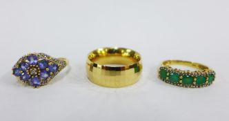 Three 14ct gold rings to include a five stone emerald and diamond ring, a tanzanite ring and a