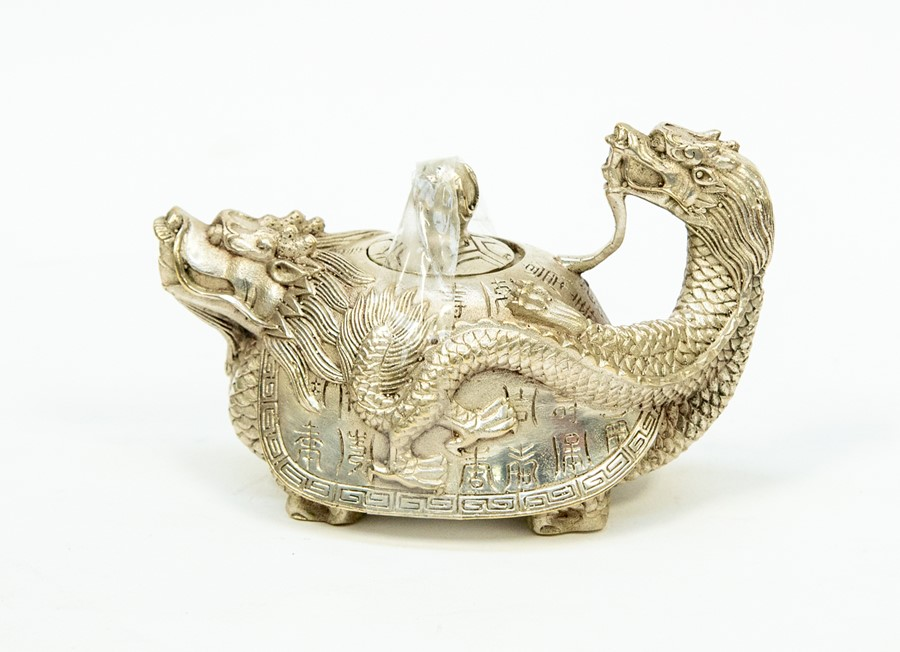 Lot 97 - A Chinese white metal novelty teapot, in the form of a dragon, decorated with Chinese script,