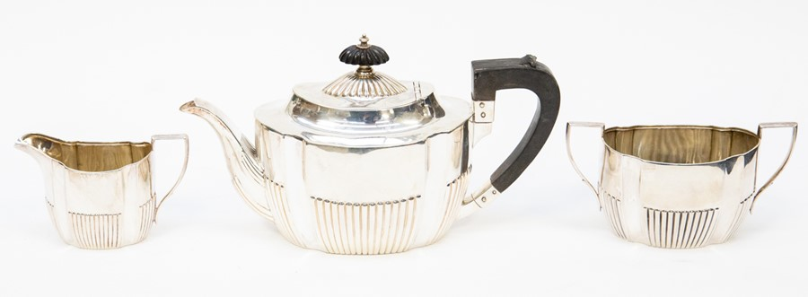 Lot 32 - A Victorian silver tea service comprising a teapot, milk jug and sugar bowl, the teapot with