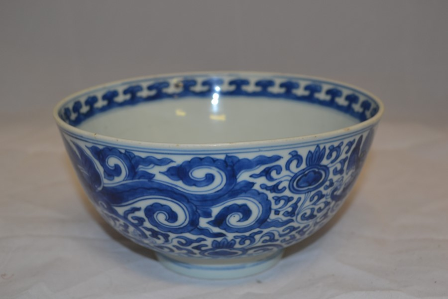 Lot 2108 - A Chinese blue and white bowl, Kangxi period, with three animated dragon spiralling through a