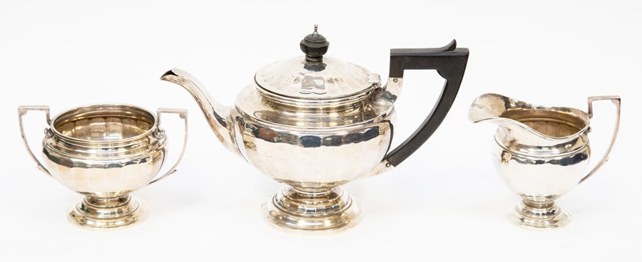 Lot 30 - A silver tea set, comprising teapot embossed fluting to body, ebonized handle, sugar bowl and milk