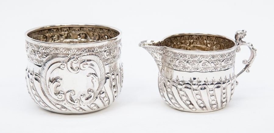 Lot 58 - A silver sugar bowl and cream jug, embossed decoration, London 1892, makerWilliam Hutton & Sons (