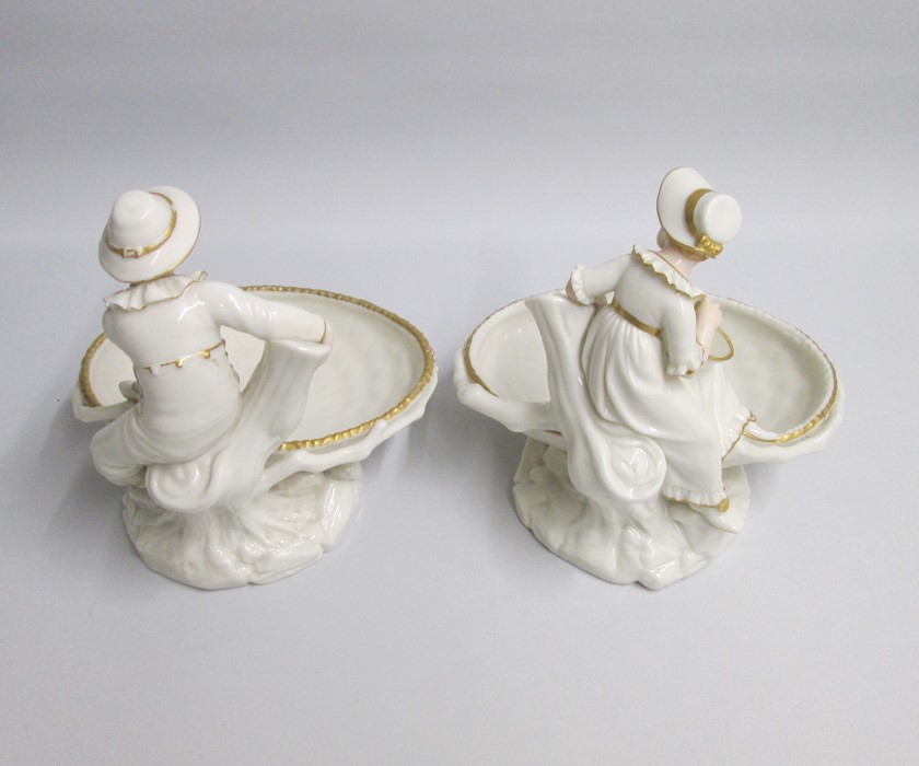 Lot 2160 - A pair of Fine Royal Worcester Figural Comports depicting a Boy and a Girl ina Hadley style
