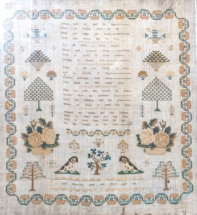 Lot 2508 - An early Victorian embroidered textile sampler, strawberry border containing spaniels, trees and
