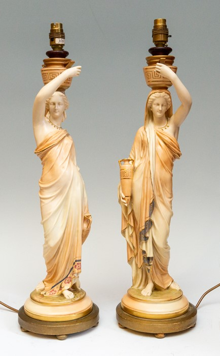 Lot 2433 - A pair of Royal Worcester blush ivory figural table lamps, in the form of a woman with two vases,