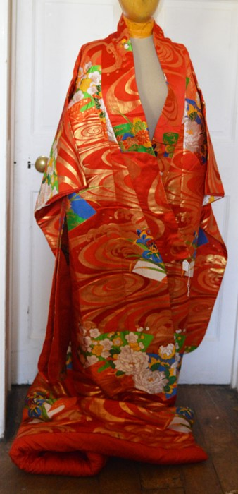 Lot 3317 - A red kimono (coat) with a vibrant design. Worn by a bride. Embellished in gold and silver thread